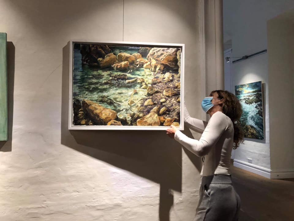 Catherine Cavallo hanging paintings